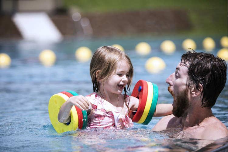 Mann planscht mit Kind im Außenbecken